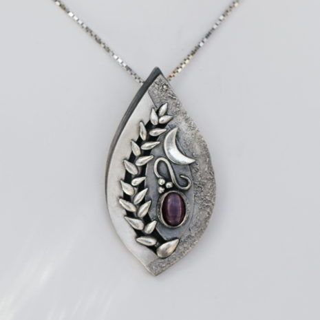 One of a kind, fine silver pendant with no detail overlooked. This elegant pendant will sure to be cherished and loved for years to come. Handmade by a local Edmonton Artist, this pendant is truly special with its nature-inspired whimsical winding vines and moon accent. Metal: Fine 99.9% Silver Pendant Stone Type: Dyed Syn. Sapphire Stone Cut: Oval Chain: Adjustable to 22″ Sterling Silver